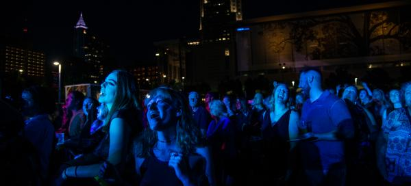 Red Hat Amphitheater attendees sing along during an evening concert