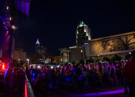 Downtown Raleigh shimmers at night in the background of a band performing at Red Hat Amphitheater