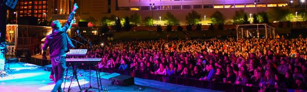 A performer behind a keyboard points to the crowd during an evening show at Red Hat Amphitheater